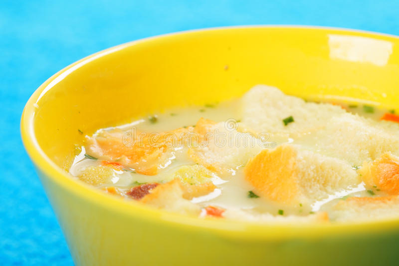 Sippets in cheese cream soup against blue royalty free stock photography