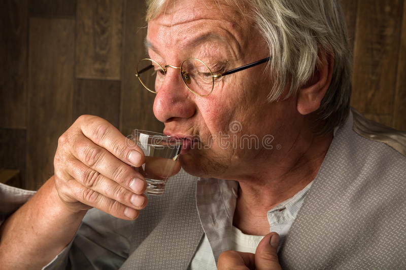 Sipping a shot glass. Gray elderly man enjoying a jenever drink in a shot glass stock photography