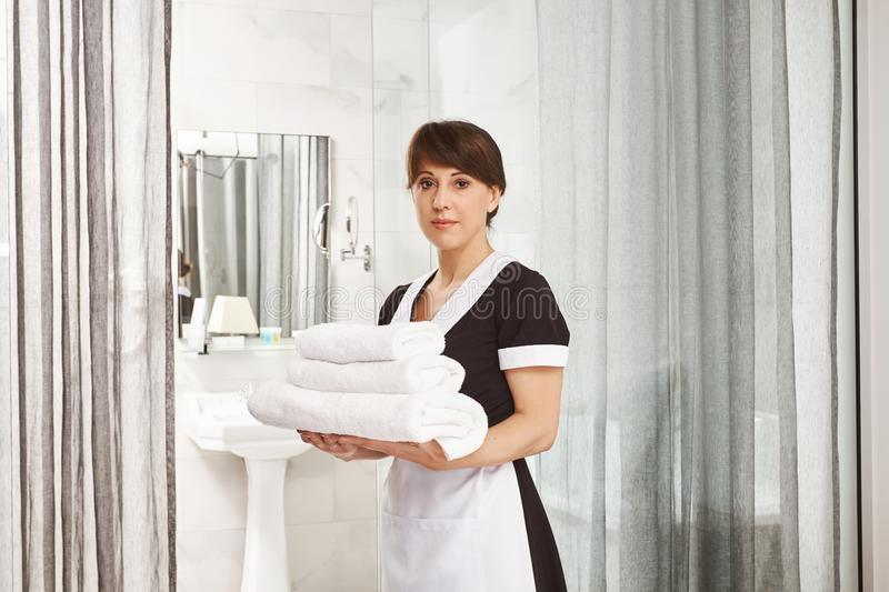 Sir, I will put extra towels in bathroom. Portrait of woman in maid uniform standing with white hotel towels near door stock image