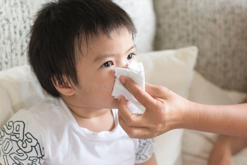 Sira de mãe à ajuda fundir o nariz asiático do ` s da criança com tecido de papel Sea foto de stock royalty free