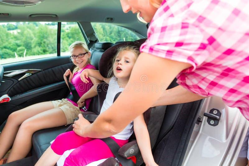 Sira de mãe à dobra acima na criança - assento da segurança do carro imagens de stock royalty free