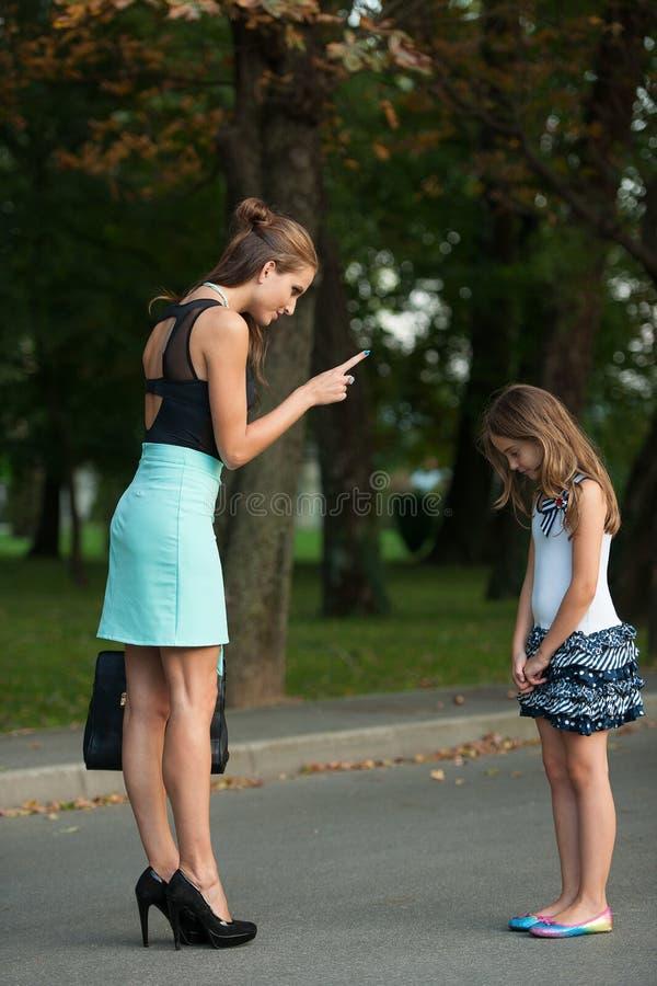Sira de mãe à fala à menina impertinente em uma rua no parque imagem de stock royalty free
