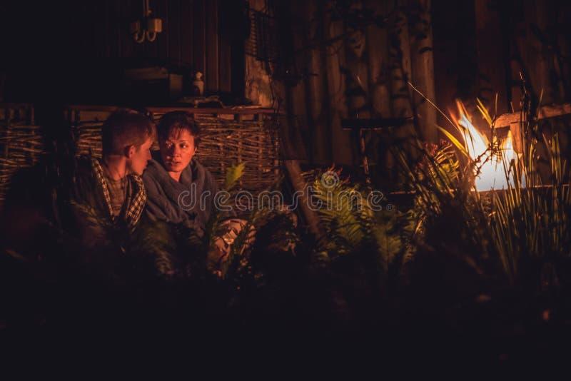 Sira de mãe à fala com seu filho maduro do adolescente em torno da fogueira na noite no campo imagens de stock