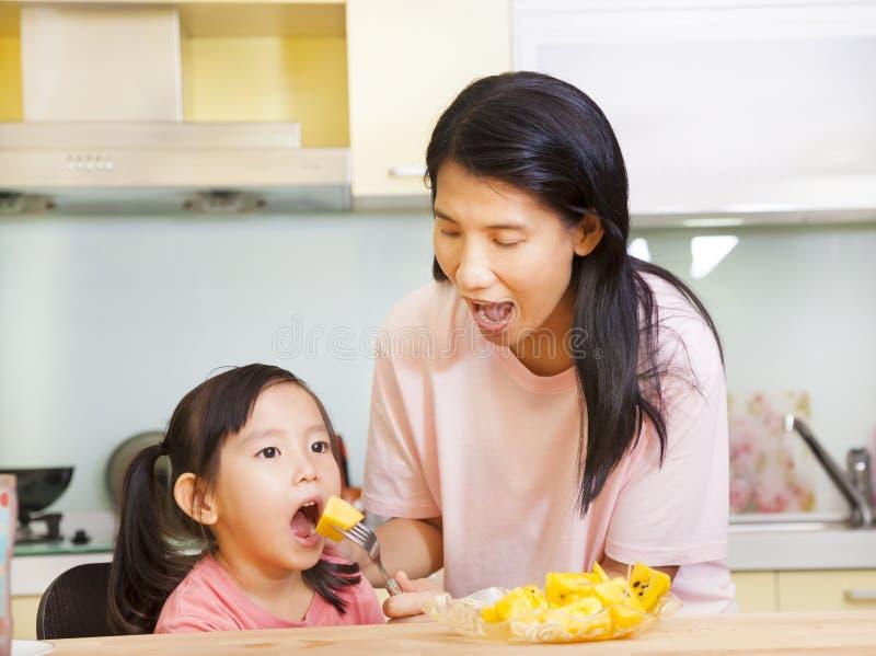 Sira de mãe à filha de alimentação que come frutos na cozinha foto de stock