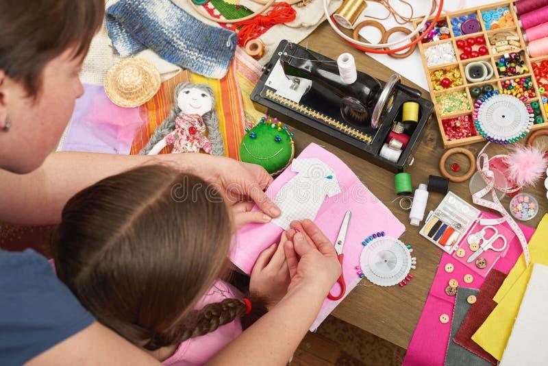 Sira de mãe à filha de ensino para costurar a roupa da boneca, vista superior, costurando acessórios vista superior, local de tra foto de stock