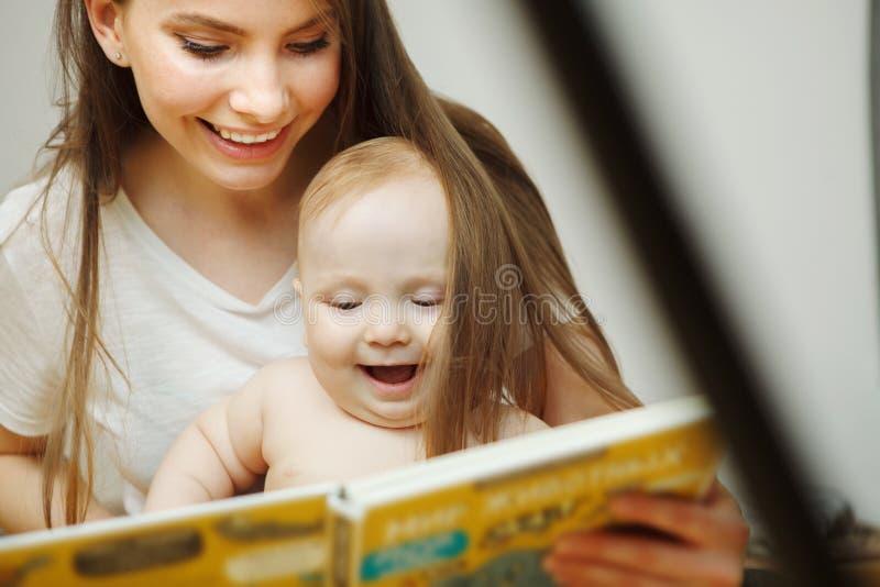 Sira de mãe à leitura ao livro colorido infantil pequeno com contos de fadas imagem de stock royalty free