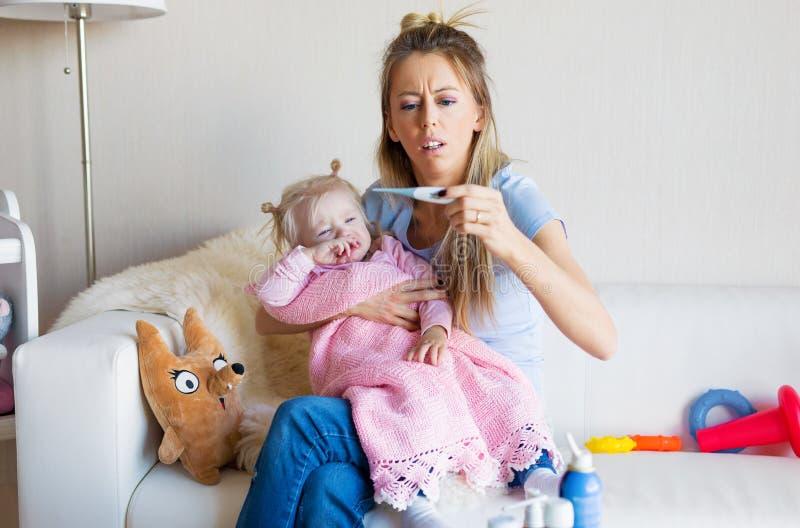 Sira de mãe à temperatura de medição de seu bebê de grito doente fotografia de stock