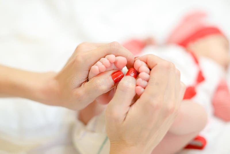 Sira de mãe às mãos delicadas com os pregos vermelhos que guardam os pés recém-nascidos do bebê imagens de stock royalty free