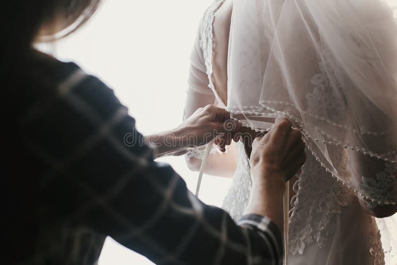 Sira de mãe às mãos que guardam fitas e que ajudam vestindo o brid bonito fotografia de stock