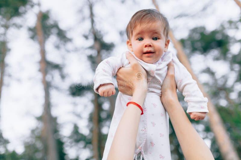 Sira de mãe às mãos que lanç acima do bebê alegre do ar alto Atividade fora saudável da criança, estilo de vida ativo e divertime imagem de stock
