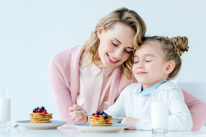 sira de mãe a abraçar a filha pequena ao comer o café da manhã junto imagem de stock