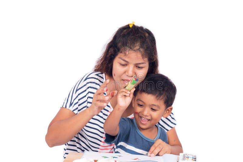 Sira de mãe ajudam seu filho que faz trabalhos de casa, pintam a cor no livro fotos de stock