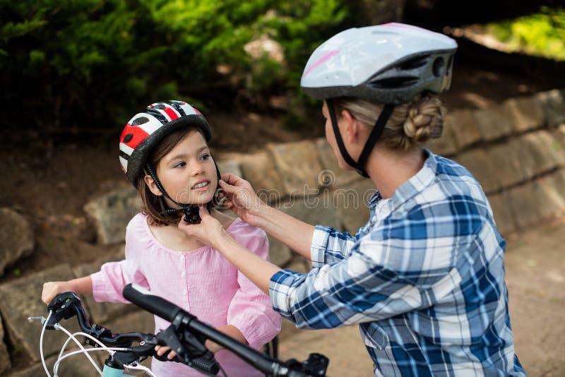 Sira de mãe a ajudar a filha no capacete vestindo da bicicleta no parque imagens de stock royalty free