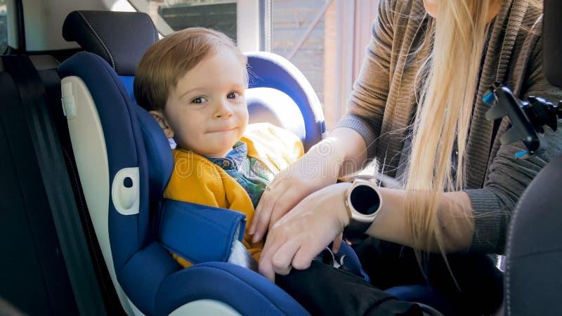 Sira de mãe a ajustar e a travar o assento da segurança das crianças do carro fotos de stock