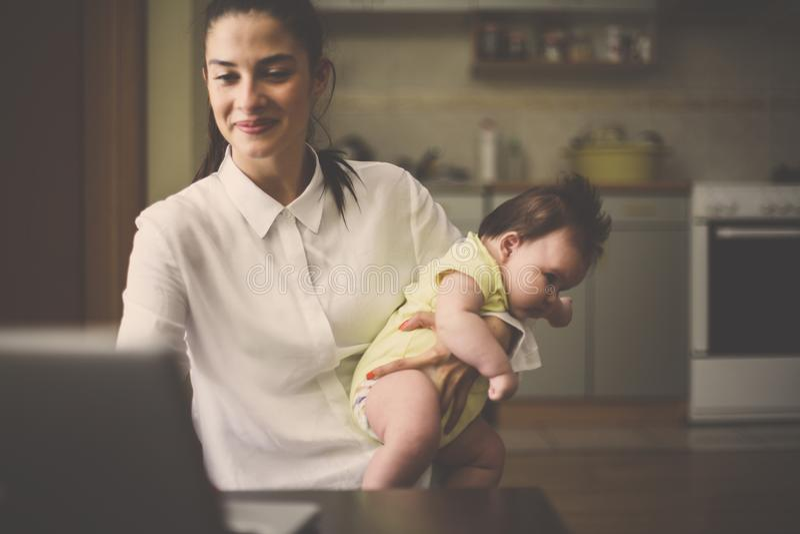 Sira de mãe ao assento na cozinha com bebê e a usar o portátil fotografia de stock