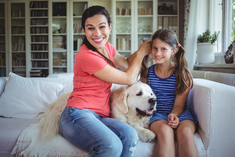 Sira de mãe ao assento no sofá e a amarrar o cabelo das filhas na sala de visitas imagem de stock