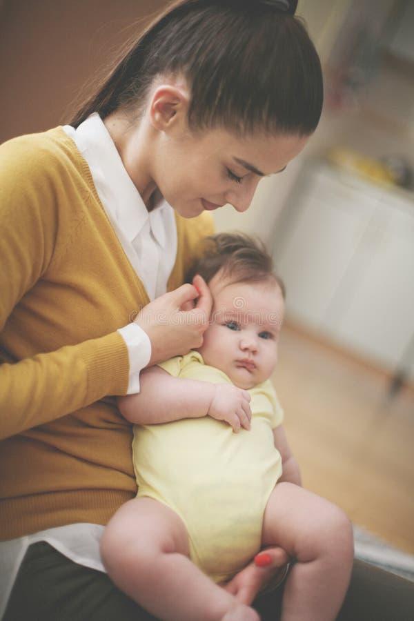 Sira de mãe ao assento no sofá e ao jogo com seu bebê pequeno foto de stock royalty free
