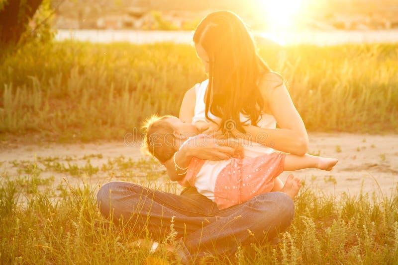 Sira de mãe ao bebê da amamentação na luz solar no por do sol fotos de stock royalty free