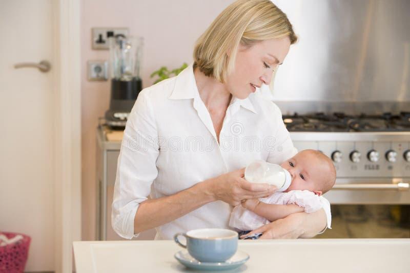 Sira de mãe ao bebê de alimentação na cozinha com café imagem de stock royalty free