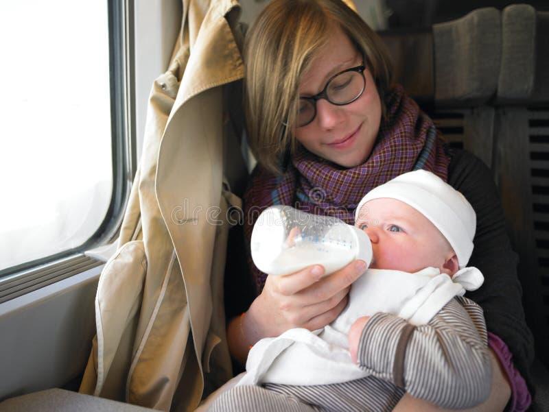 Sira de mãe ao bebê de alimentação no trem foto de stock