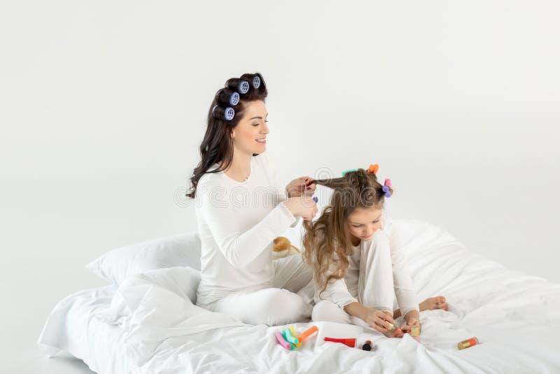 Sira de mãe ao cabelo de ondulação à filha que aplica o verniz para as unhas ao sentar-se na cama foto de stock royalty free