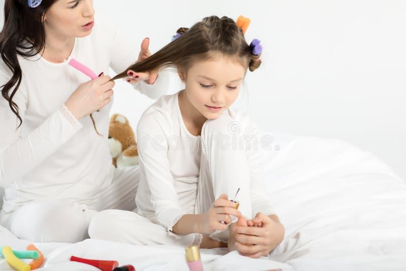 Sira de mãe ao cabelo de ondulação à filha que aplica o verniz para as unhas nas unhas do pé fotografia de stock royalty free