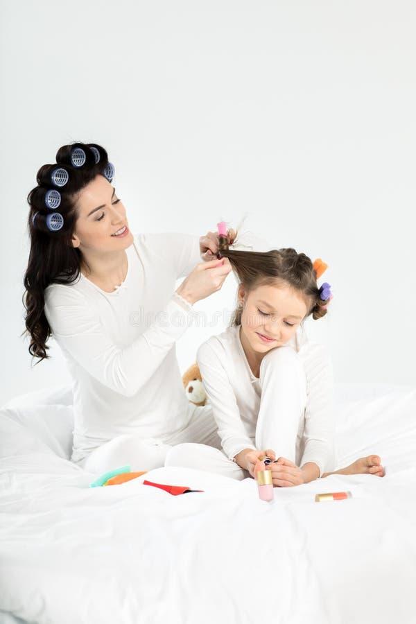 Sira de mãe ao cabelo de ondulação à filha que aplica o verniz para as unhas nas unhas do pé imagens de stock
