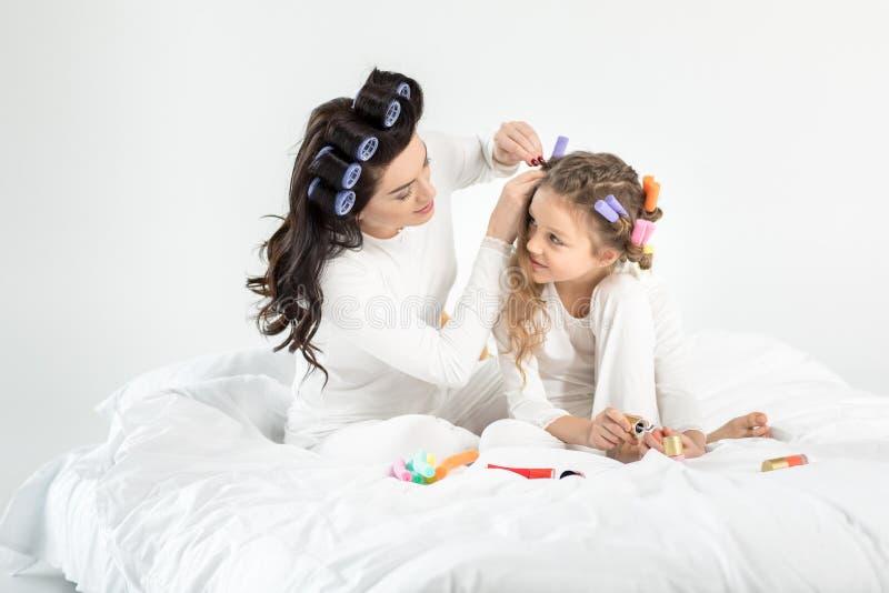 Sira de mãe ao cabelo de ondulação à filha que aplica o verniz para as unhas nas unhas do pé foto de stock royalty free