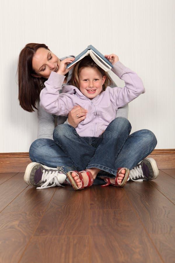 Sira de mãe ao divertimento da instrução da filha que aprende ler fotografia de stock royalty free