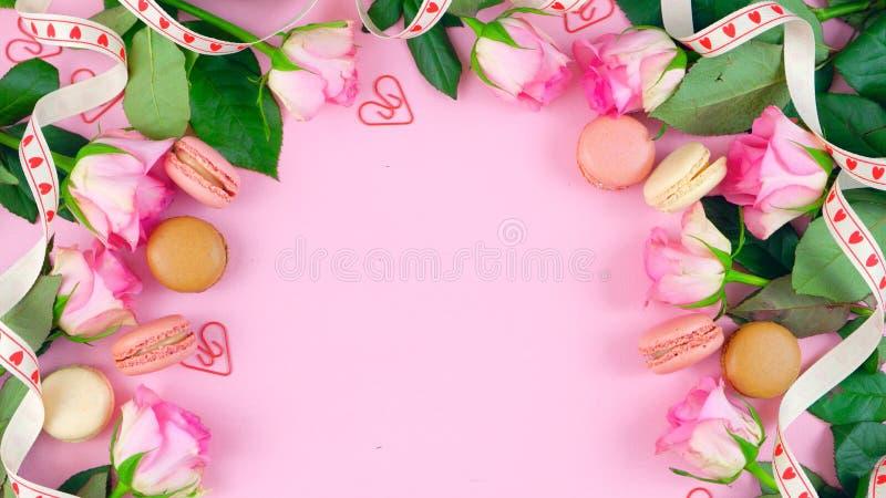Sira de mãe ao fundo do dia do ` s de rosas e de cookies cor-de-rosa do macaron na tabela de madeira cor-de-rosa ilustração stock