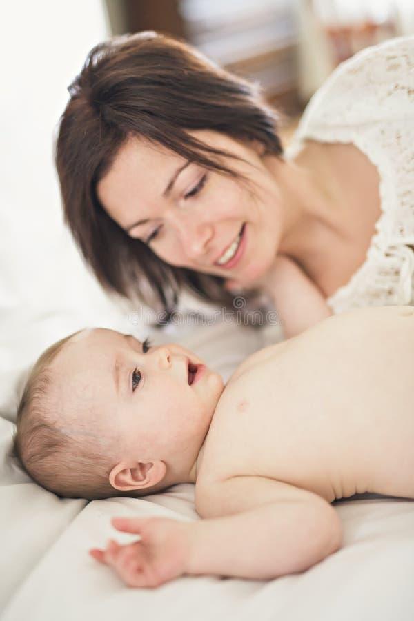 sira de mãe ao jogo com seu bebê no quarto foto de stock