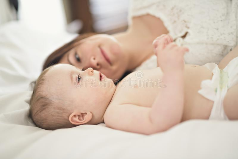 sira de mãe ao jogo com seu bebê no quarto fotos de stock