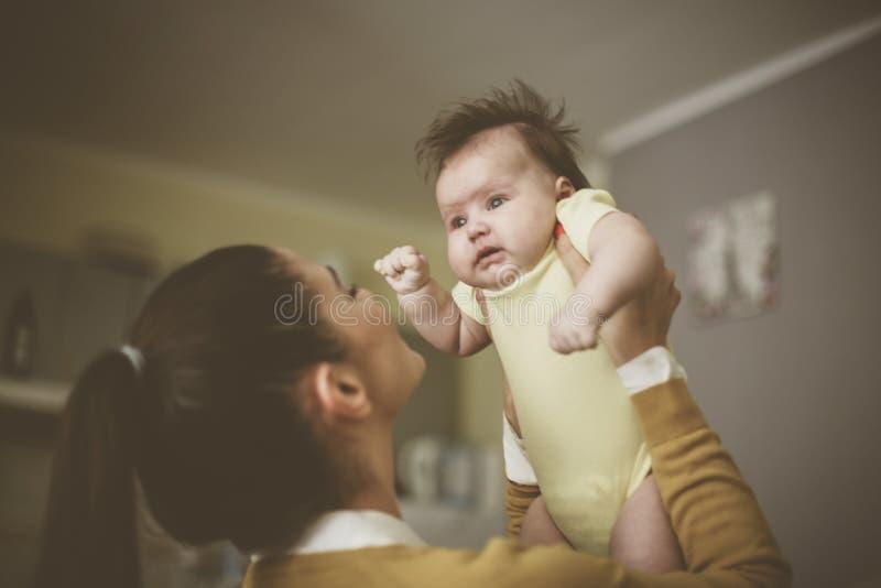 Sira de mãe ao jogo com seu bebê pequeno e a realizar nas mãos fotos de stock