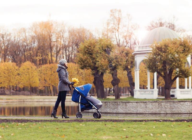 Sira de mãe ao jogo no parque com seu bebê da criança Mamã e filho sobre o fundo sazonal do outono imagens de stock royalty free