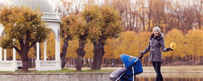 Sira de mãe ao jogo no parque com seu bebê da criança Mamã e filho sobre o fundo sazonal do outono fotografia de stock