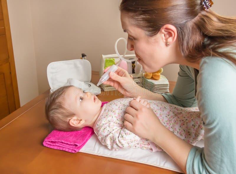 Sira de mãe ao muco da limpeza do bebê com aspirador nasal imagens de stock royalty free