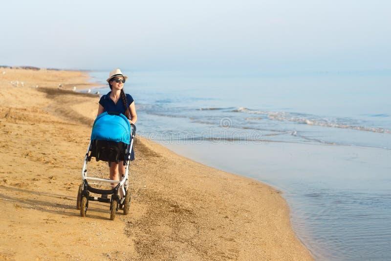 Sira de mãe ao passeio com o carrinho de criança na praia do mar imagens de stock
