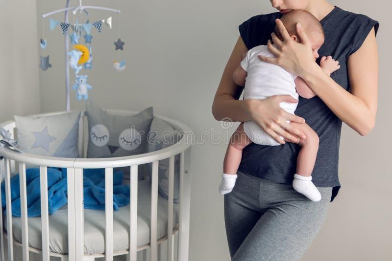 Sira de mãe ao sono na caixa de seu filho imagens de stock