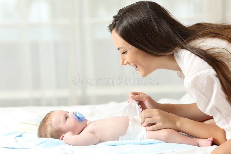 Sira de mãe ao tecido em mudança a seu bebê foto de stock royalty free