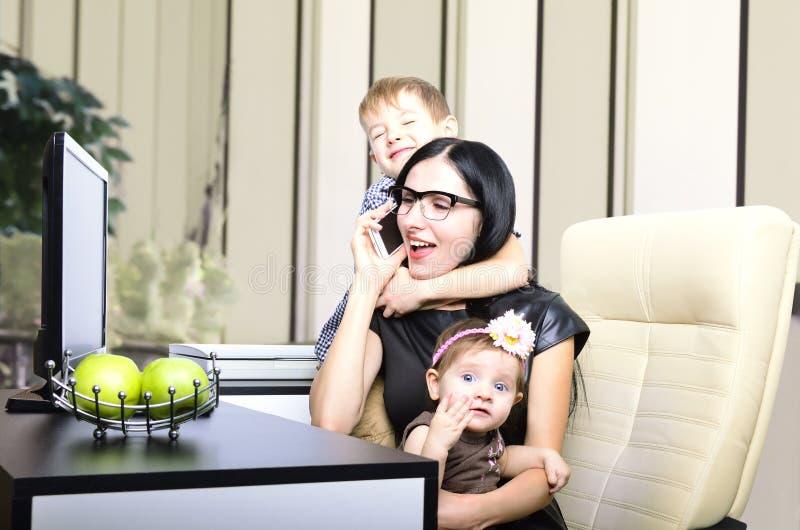 Sira de mãe ao trabalho no computador com suas crianças imagens de stock