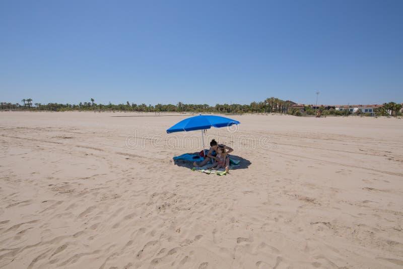 Sira de mãe a aplicar a proteção solar na criança sob o guarda-chuva na praia imagens de stock
