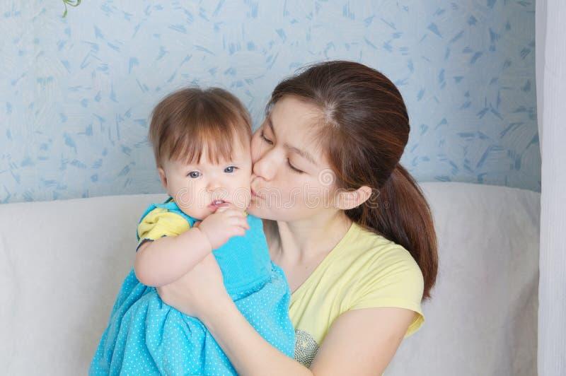 Sira de mãe a beijar a criança, a mulher de sorriso feliz com bebê pequeno, a família multinacional com mamã asiática e a filha imagem de stock