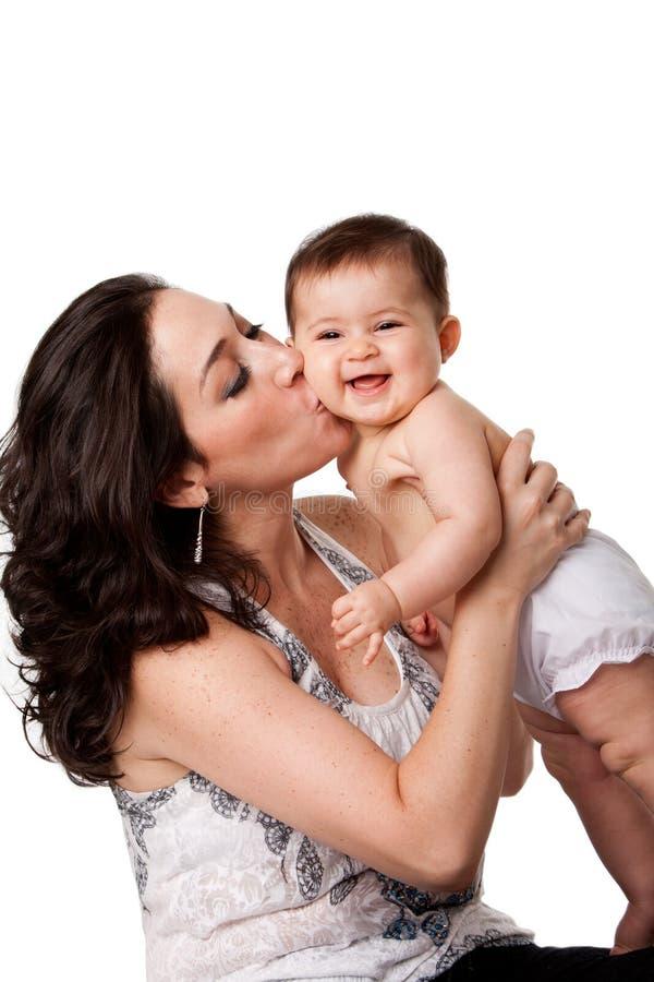 Sira de mãe a beijar o bebê feliz no mordente imagem de stock