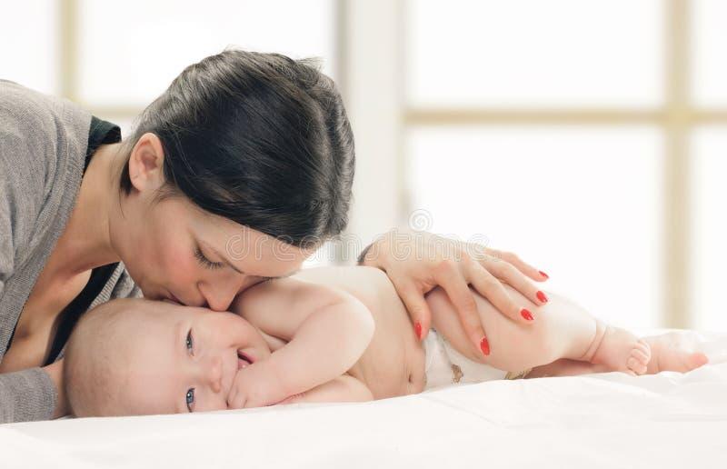 Sira de mãe a beijar o bebê feliz no mordente foto de stock