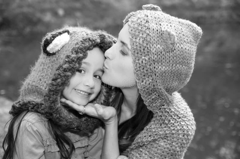 Sira de mãe com os hoodies vestindo da filha e a roupa morna que sentam fora o abraço felizmente, fundo verde da natureza fotos de stock royalty free