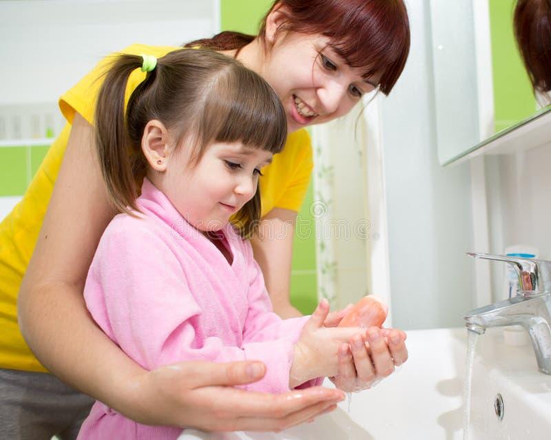 Sira de mãe e caçoe à filha que lava suas mãos no banheiro Cuidado e interesse para crianças imagem de stock