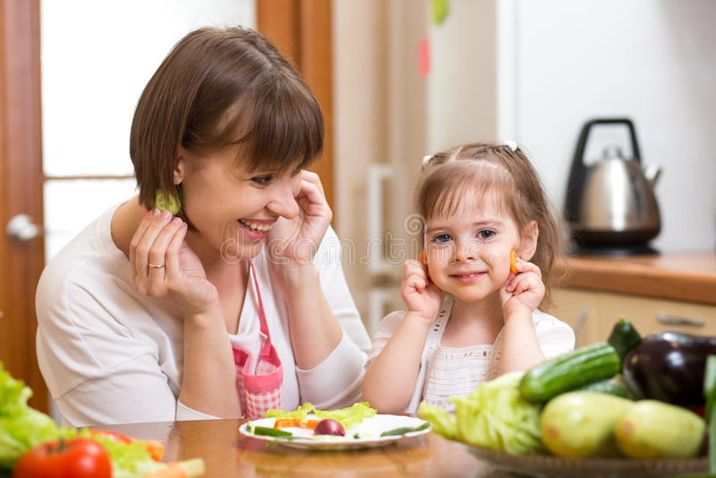 Sira de mãe e caçoe a cozinhar e a ter o divertimento na cozinha foto de stock