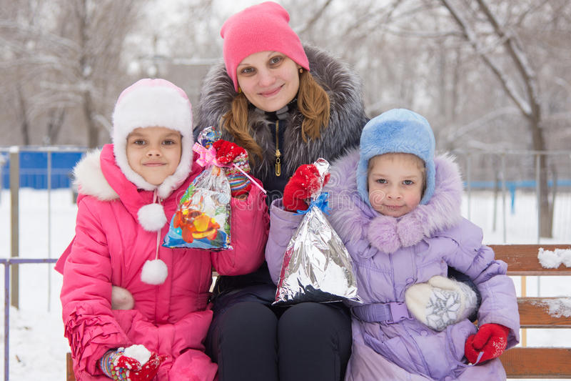 Sira de mãe e duas filhas com os presentes do Natal em suas mãos fotografia de stock
