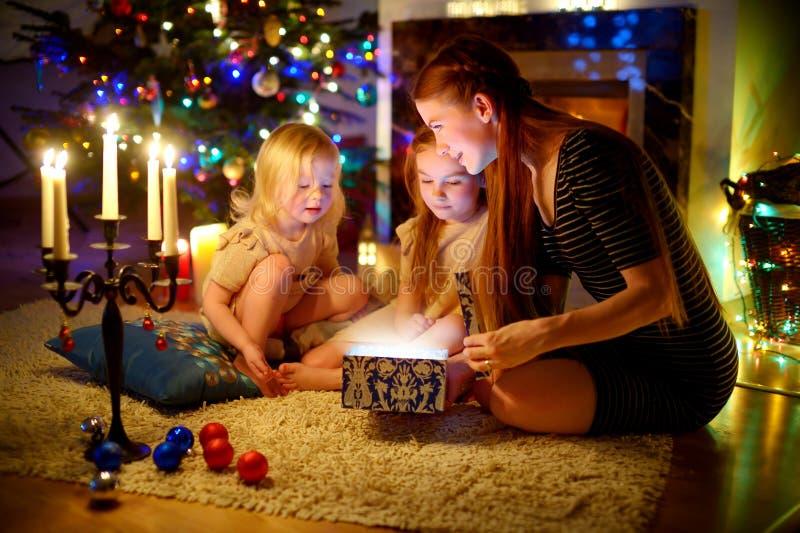 Sira de mãe e duas filhas pequenas que abrem um presente mágico do Natal imagens de stock