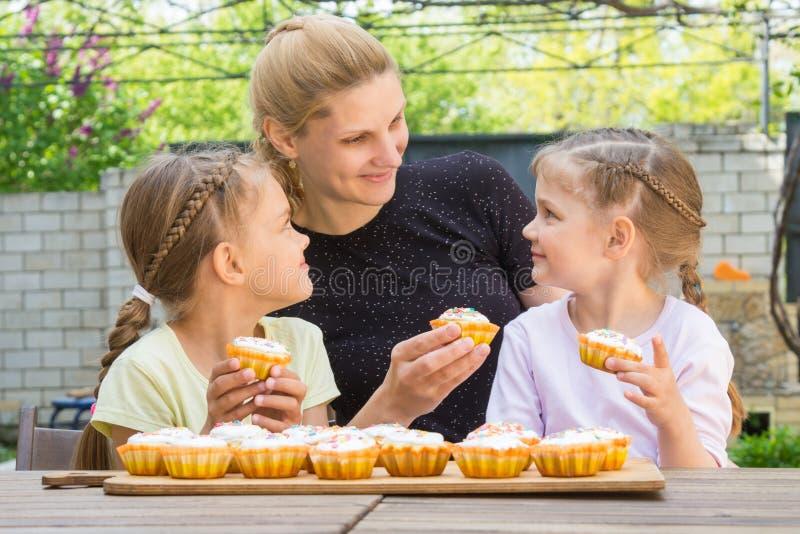 Sira de mãe e duas filhas que sentam-se na tabela com os queques da Páscoa em suas mãos imagens de stock